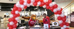 Rocky posing with Campus Recreation staff at the Student Recreation Center info counter with a big red and white balloon arch over them.