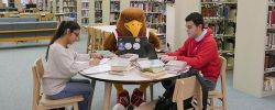 Picture of Rocky sitting at a table in the library with two students with laptops and books on the table.