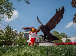 Rocky standing with the Red Hawk Statue.