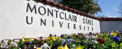 Picture of the Montclair State University sign at the campus front entrance with summer flowers.