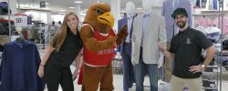 A picture of Rocky the Red Hawk and two Montclair State University students at the JCPenney professional apparel discount event show some of the clothing available at a discounted price.