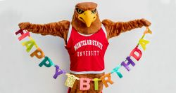 Rocky the Red Hawk holding up a colorful Happy Birthday sign.