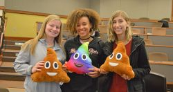 Picture of three students holding their poop emoji pillows they created.