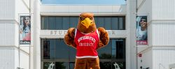 Rocky the Red Hawk, hands on hips, standing in front of the Student Center on a sunny day