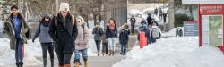 Picture of students walking on campus in winter with snow on the ground.