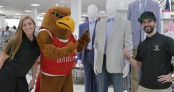 Picture of two Montclair State students with Rocky the Red Hawk admiring business apparel available at JCPenney.
