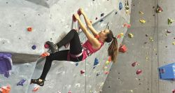 Picture of a woman climbing on a rock climbing wall.