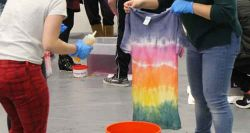 Picture of a student holding a tie dye t-shirt.