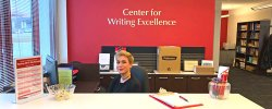 Student sitting at the desk of the Center for Writing Excellence