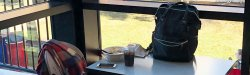 Picture of a backpack, cell phone and clothes left unattended at a cafeteria table.
