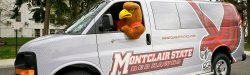 Rocky the Red Hawk sitting in the driver's seat looking out the window of a Montclair State athletics van.