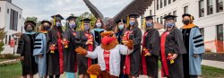 Picture of Rocky the Red Hawk with the 2020 Nursing School graduates and staff in front of the campus Hawk statue.