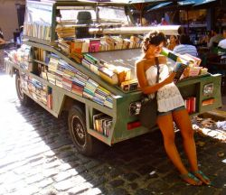 Photo of student reading and leaning against pick-up truck bookstore filled with books in Argentina.