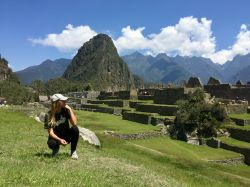 Photo of study abroad student Brianna Rivera kneeling on the grass in Peru.