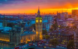 Photo of sunset over london with Big Ben and surrounding buildings lit up.