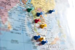 Photo of map with colorful pins marking Southeast Asia countries.