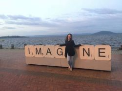 Student in front of sign reading Imagine