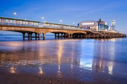 The lights of Bournemouth Pier at night reflected in the wet sand on the beach in Dorset, England