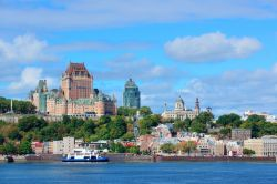 Quebec City skyline over river with blue sky and clouds.