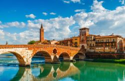 Sunny summer view of Bridge Ponte Pietra in Verona on Adige river.