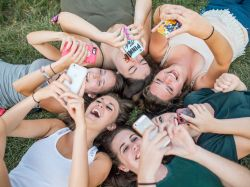 Female Montclair State University students laying in a circle while taking selfies with cellphones.