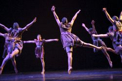 Photo of six dancers leaping toward a central point.