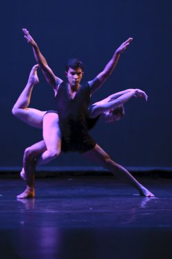 Photo of two dancers, one supporting the other.