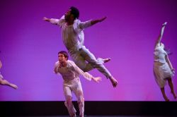 Photo of dancers in white leaping through the air.