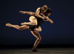 Photo of two dancers, one supporting the other, in dramatic pose.