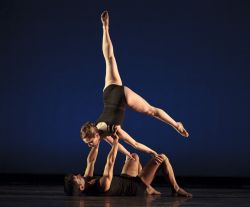 Photo of two dancers, one lifted upside-down with leg in the air.