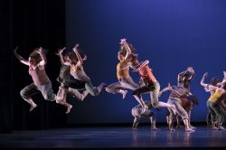 Photo of large group of dancers in formation and jumping.