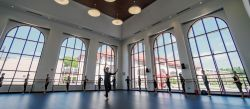 Dancers practicing in front of large windows in large dance studio