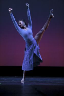 Photo of dancer performing high kick.