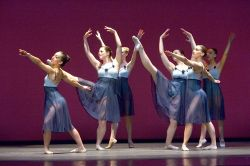 Photo of six dancers in flowing lavender skirts.