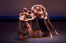 Photo of dancers in tight group, arms interlocked.