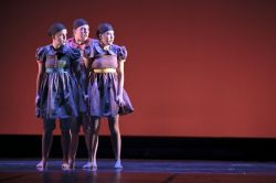 Photo of trio of dancers standing close on stage.