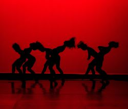 dancing silhouettes in front of piercing red background