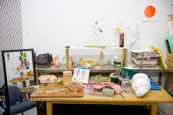 Photo of MFA studio workspace with lots of art supplies on table.