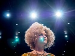 Student Actress performing in production of Hair standing with stage lights in background