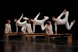 Dancers posing in unison on benches