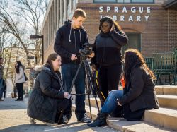Four journalism students with camera outside Sprague Library