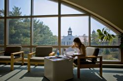Student studying in library in front of large window overlooking College Hall.