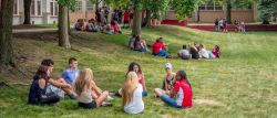 Photo of small groups of students sitting on campus green during orientation.