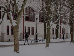 Student walking along the pathway next to the Student Center Quad in the snow.