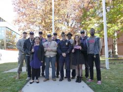 Veterans and students standing together at a flag raising ceremony.