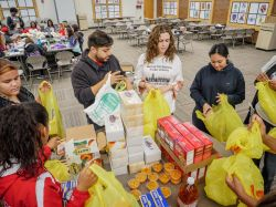 Montclair State University students organizing canned goods as part of volunteering.