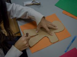 A student tracing a person on some construction paper.