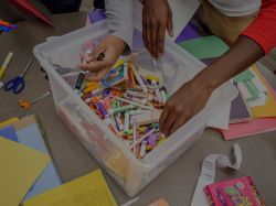 Students reaching into a box of markers and crayons.