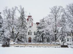 Main entrance of College Hall and surrounding trees blanketed in snow.