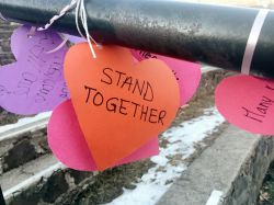 Some paper hearts on a railing with inspirational messages.
